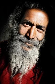 Старший индийский мужчина, глядя на камеру.