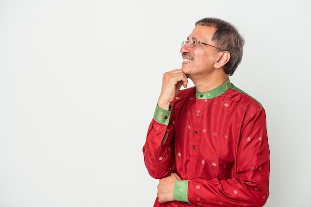 疑わしいと懐疑的な表現で横向きに見える白い背景に分離されたインドの衣装を着た年配のインド人男性。