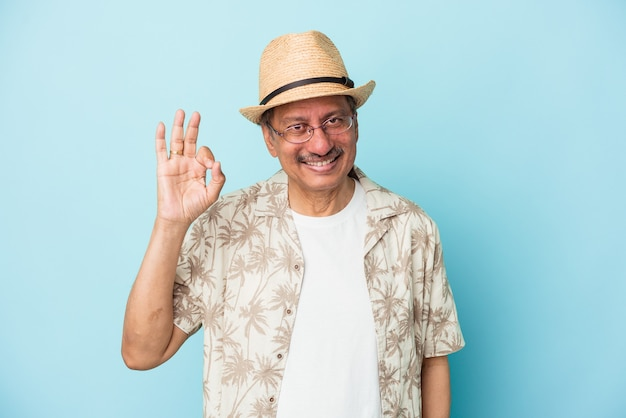 Senior indian man wearing summer clothes isolated on blue background senior indian woman wearing a african costume isolated on white background cheerful and confident showing ok gesture.