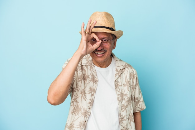 Senior indian man wearing summer clothes isolated on blue background senior indian woman wearing a african costume isolated on white background excited keeping ok gesture on eye.