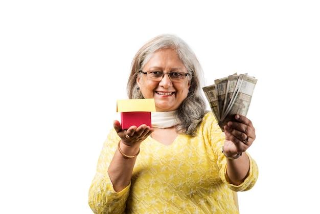 通貨コインを保存または保持または計算するシニアインドまたはアジアのビジネスウーマン。ビジネス、金融、投資の概念