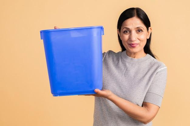 空の青いコンテナを保持している年配のインドの女性