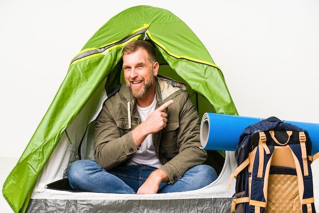 白い壁に隔離されたテントの中の先輩が笑顔で脇を向いて、空白のスペースで何かを見せています。
