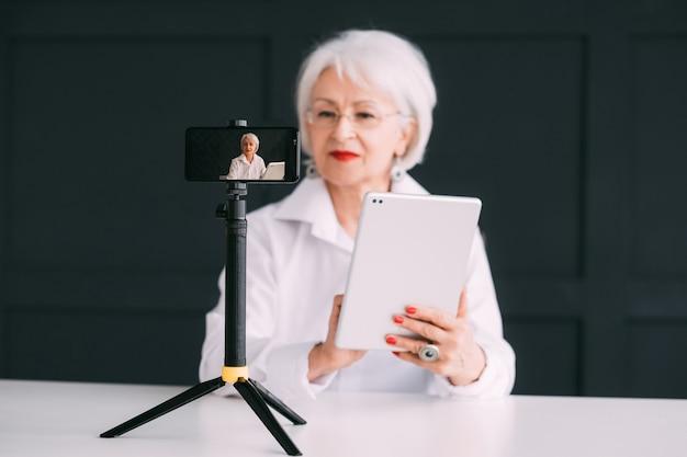 Старший блоггер леди. онлайн-бизнес-тренер. стильная пожилая женщина потоковое видео.