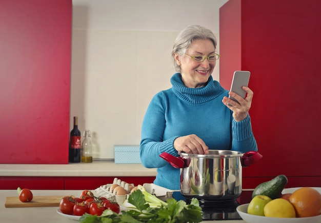 Senior lady cooking and checking her smartphone