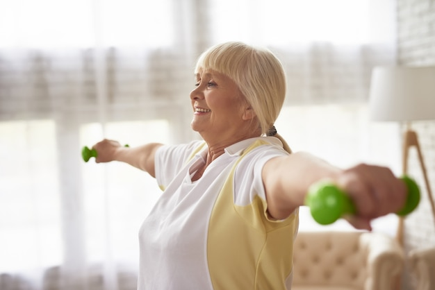 Senior lady dumbbells exercise workout at home.
