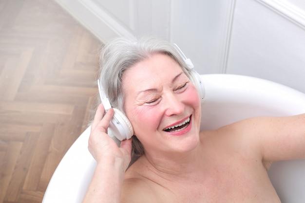 Senior lady enjoying a bath with music