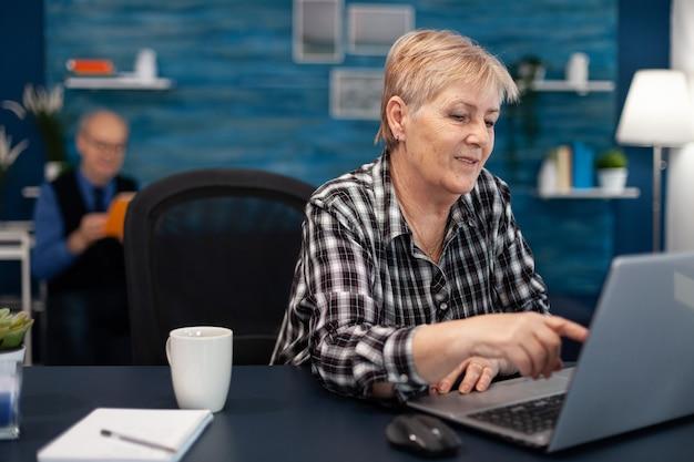 인터넷 검색을 하는 동안 컴퓨터 화면을 가리키며 일하고 있는 고위 여성 기업가. 집 거실에 있는 노부인은 실내 책상에 앉아 의사 소통을 위해 모더 테크놀로이 노트북을 사용합니다.
