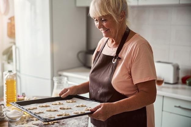 Senior lady having a sheet of dough ready for baking