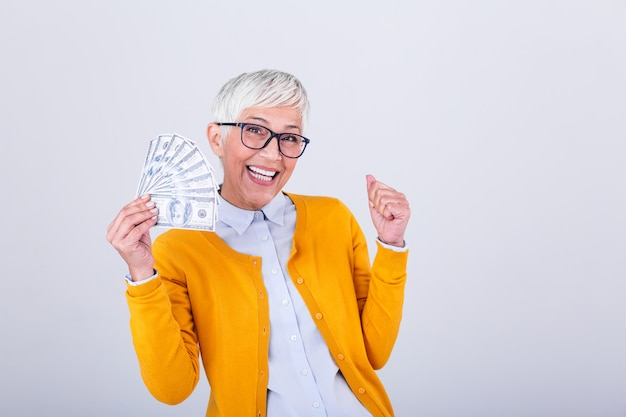 Senior lady holding a bunch of $100 bills with surprised facial expression.