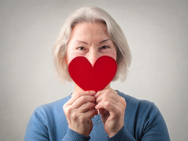 Senior lady holding a paper heart