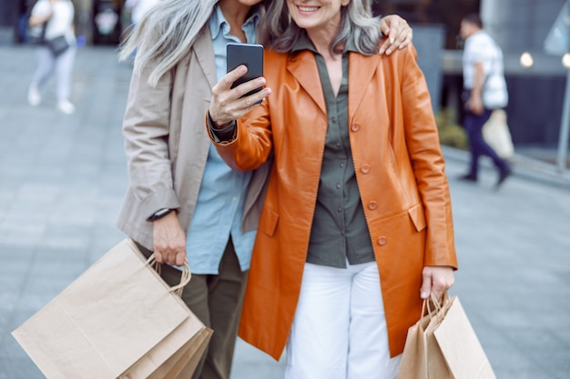 革のジャケットを着た年配の女性と買い物の仲間は、現代の街の通りで自分撮りをします