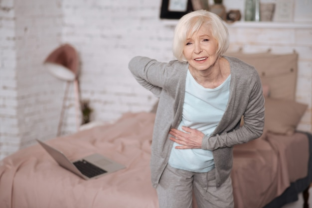 Senior lady leaning because of terrible backache while standing at home.