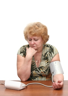 Senior lady measures arterial pressure , use digital tonometer . isolated. upset by instrument readings.
