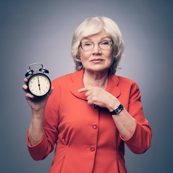 Senior lady pointing to alarm clock showing time of deadline