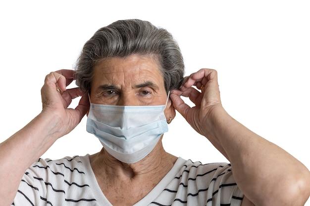 Старшая дама надевает медицинскую маску