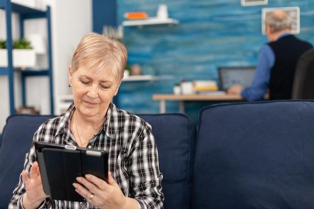 전자 책을 읽고 소파에 집에서 휴식 수석 여자