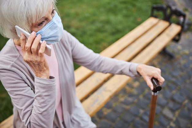 지팡이로 벤치에 앉아 전화 통화를하면서 의료 마스크를 쓰고 수석 아가씨