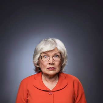 회색 배경에 안경을 통해 응시하는 노인 여성