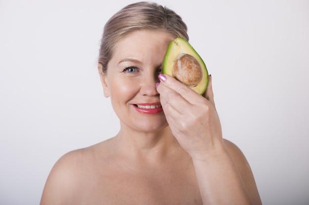 Старшая дама с раздетыми плечами закрывает глаза авокадо, улыбаясь в камеру на белой стене в студии