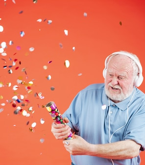 Senior listening music and popping confetti