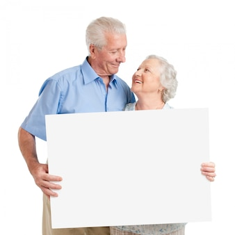 Senior lovely couple holding together a white board isolated on white