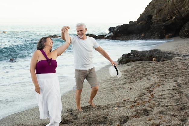 Старшие влюбленные проводят время вместе на пляже Бесплатные Фотографии