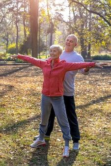 秋の公園で一緒に運動する年配の男性と女性
