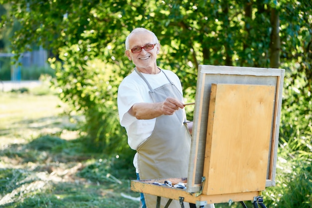 Senior male artist drawing picture at park using paint palette, easel and canvas.