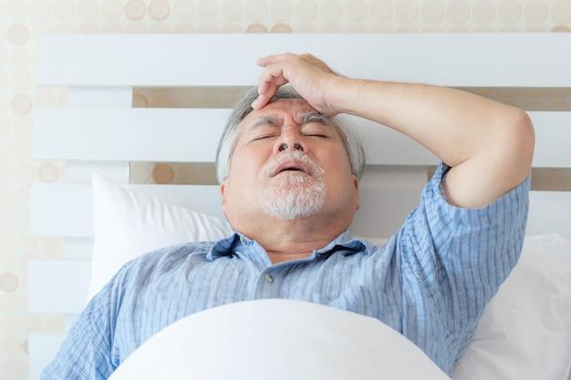 自宅でのシニア男性アジア人頭痛-シニア心臓病