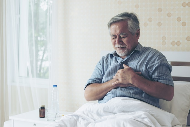Senior male asian suffering from bad pain in his chest heart attack at home - senior heart
