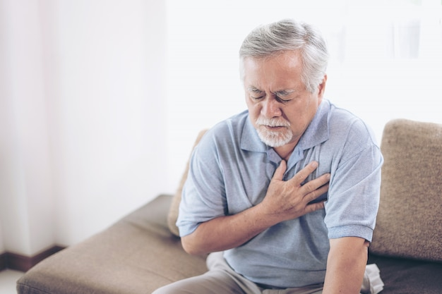 Senior male asian suffering from bad pain in his chest heart attack at home