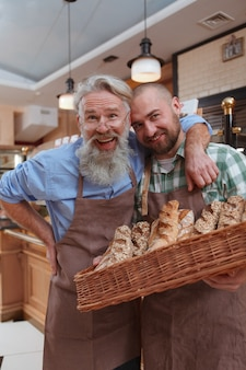 Senior male baker and his son laughing posing with basket of freshly baked bread