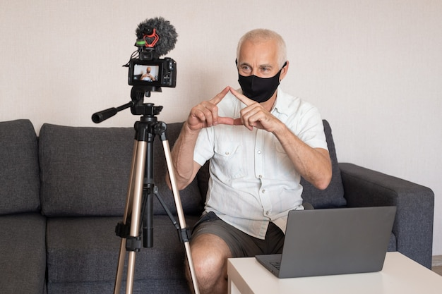 Senior male blogger in mask at home recording video at home, blogging, videoblog and people concept