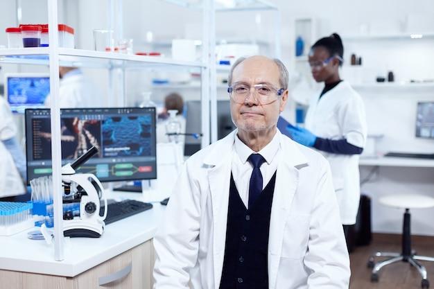 保護メガネをかけたカメラを見ている年配の男性化学者。白衣を着た年配の科学者が、アフリカの助手を背景に新しい医療用ワクチンの開発に取り組んでいます。