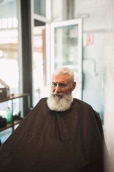 Senior male client with cape in barbershop