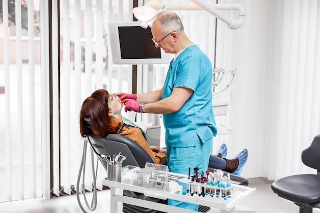 若い女性の歯の歯科チェックを行う彼のクリニックでシニア男性歯科医。歯科のコンセプト