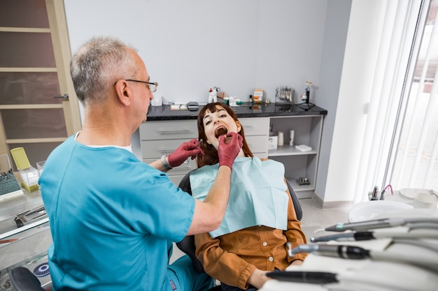 現代の歯科医院での口腔検診中の若い女性患者とシニア男性歯科医