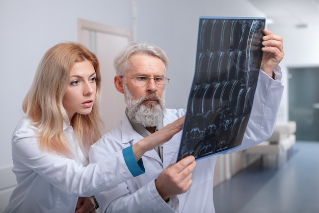 Senior male doctor and his young female intern examining mri scan together