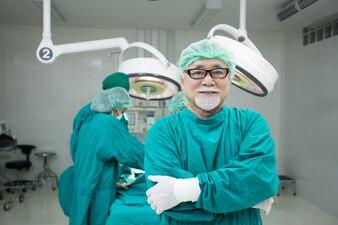 手術室の背景に魅力的な笑顔でカメラを探している上級男性医者。
