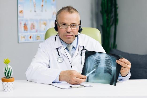 グループ会議のビデオ通話仮想ウェブカメラチャットアプリ中にコロナウイルスのパンデミックについてヘッドセットビデオ会議を行うシニア男性医師