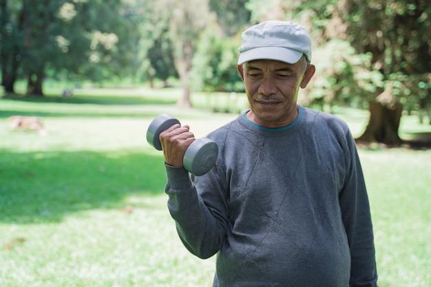 Старший мужчина делает упражнения в парке и держит гантели