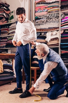 Senior male fashion designer taking measurement of customer's leg in the shop