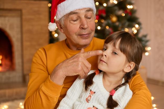 サンタの帽子をかぶった年配の男性が孫娘を抱きしめ、指で鼻を触り、おじいちゃんがクリスマスイブに隠れた小さな孫と楽しんで、お祭りの部屋でポーズをとる。