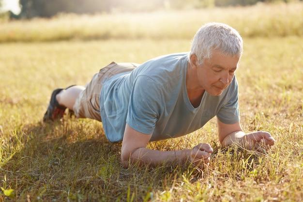 Старший мужчина делает отжимания или доску на зеленой траве, занимается спортом на открытом воздухе, имеет гибкое тело в старости, любит спортивные упражнения, наслаждается спокойной атмосферой и красивой природой. концепция благополучия.