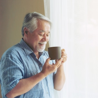 Senior male , old man feel happy drinking coffee in the morning , enjoying time in his home indoor background - lifestyle senior happiness concept