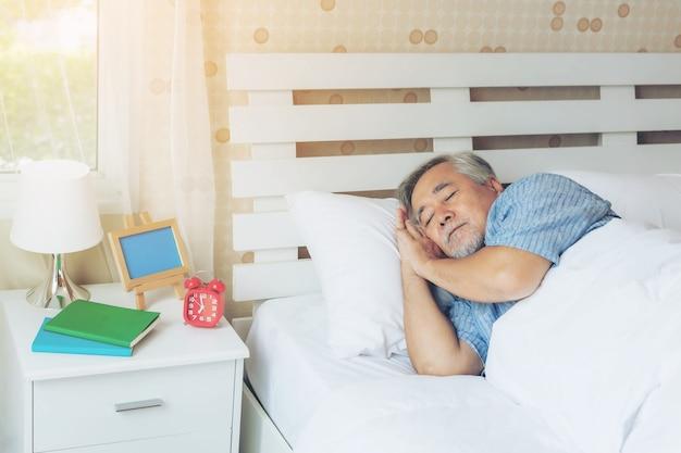 シニア男性、朝の白いベッドルームの枕で寝ている老人-ライフスタイルシニア男性健康コンセプト
