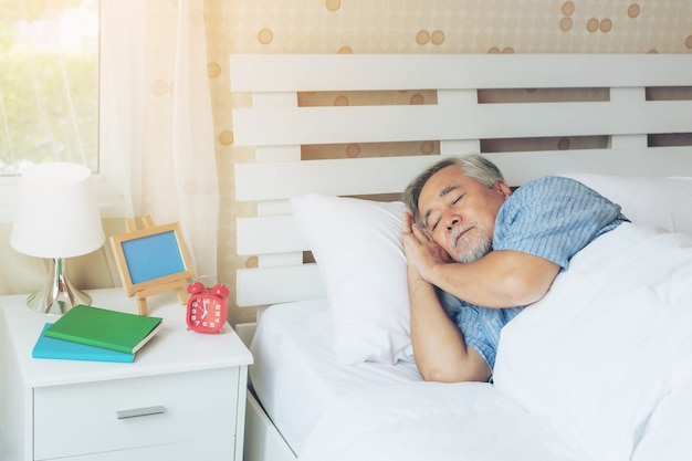 Senior male , old man sleeping on the pillow on white bed room in the morning - lifestyle senior male good health concept