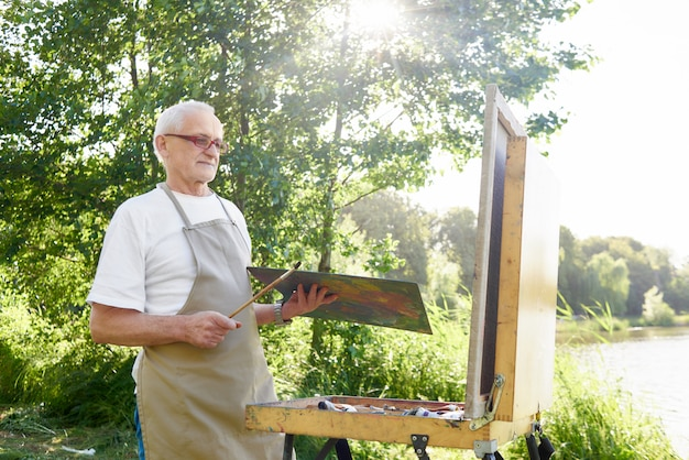 Senior male painter, standing with painting brush and palette of colors in hand, picking up paint to picture in rays of sun.