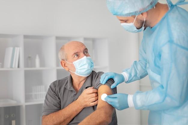 Senior male patient getting vaccinated for coronavirus